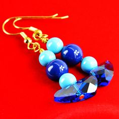 You'll be one cool customer in these two-tone blue Swarovski crystal and pearl earrings. Each earring features a row of 6mm and 8mm solid Swarovski crystal pearls that ends in a 20mm cobalt blue boomerang-shape Swarovski crystal wing. The earring descends 1 inch from the ear wire. A treat for yourself or an affordable gift for the blue crystal lover in your life.  The Smallest Planet Guarantee  All Smallest Planet jewelry is handmade by me, Sara Kelly, in my home studio in San Diego, Cali...