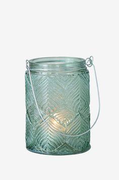 Dekorativ lysestage af glas med løvmønster i relief. Håndtag af metal. Passer lige så godt at hænge udenfor som på terrasse- eller altanbordet. Beregnet til fyrfadslys. Ø ca. 8 cm. Højde ca. 12 cm + 9 cm håndtag.