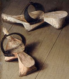 """In the Arnolfini Portrait of 1434, these pattens ( german: """"Trippen"""")have been put off inside the house. Pattens were worn during the Middle Ages outdoors and in public places over (outside) the thin soled shoes of that era. Pattens were worn by both men and women"""