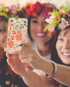 Three guests smile for a selfie. The image (and the flower phone case, which could be gifted to guests as favors) makes for a sweetmemento of the day of fun.