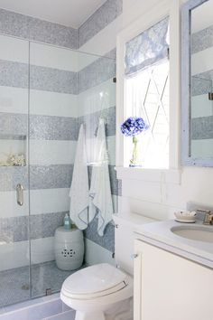 Gray and white bathroom, striped tile, glass door, white vanity, ceramic garden stool.