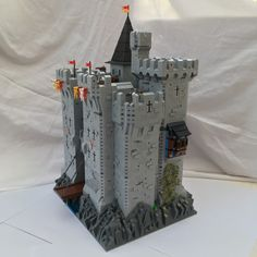 Lego MOC Castle side angle view of gatehouse and rear towers. Shows large rear tower and turret as well as rocky base and blue & black Tudor windowed protrusion from side rear.