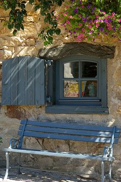 pretty window with shutter open to catch the sunlight and a matching bench ....serene setting in Lavaudieu, France