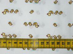 Katoenen stof met een print van kleine gele eendjes op een witte achtergrond