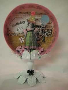 Altered art. Shadow box in a circle cap.  An old candle stick is used as the stand.