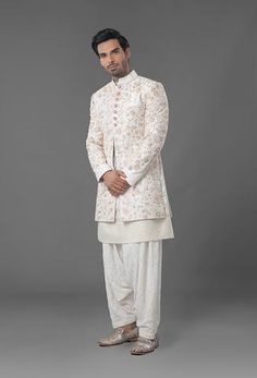 Sherwani is featured in ivory colour in raw silk fabric with dull gold zari and nakshi embroidery. Kurta and salwar is made of ivory color chikan fabric. Wedding Kurta For Men, Wedding Dresses Men Indian, Groom Wedding Dress, Indian Wedding Wear, India Fashion Men, African Men Fashion, Indian Fashion, Mens Fashion, Pathani Kurta Men