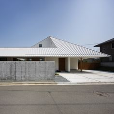 House in Sanbonmatsu, Kagawa, by Hironaka Ogawa with chunks missing from its sloping roof to reveal a central open-air courtyard.