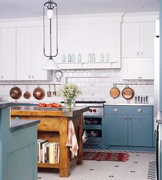 Chunky Wooden Kitchen Island - Cool blue cabinets ground this light, airy kitchen. The chunky wooden island warms the space with the look of an antique furniture piece.