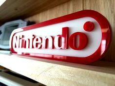 These signs are laser cut from acrylic and assembled here in shop. This display sign is themed after the Nintendo logo. Respect your collection. These signs are perfect to put in your mancave, to label your collection, or even use in your retail game shop! We make the signs to order, so there is a small wait time for display signs after purchase.  Small Size - 7.5 x 2 Medium Size - 15 x 4  Large Size - 30 x 8   You will only receive the display sign and nothing else pictured.
