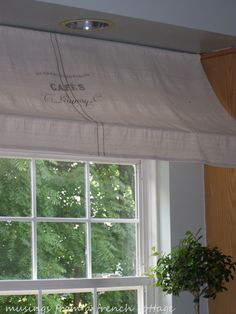 tutorial for awning   Here is what you will need:  -2 tension rods wide enough to fit between your cabinets  -a canvas drop cloth or other similar fabric of your choice  - black fabric paint and a paintbrush or black fabric marker  - blue painters tape
