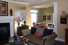 The living room paint color is Sherman Willams Blonde. The kitchen and dining room walls are Lowes Olympic Sweet Annie. The orange-ish colored walls I mixed myself. The closest match to the orange paint is Behr Maple Glaze at Home Depot.
