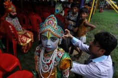 """""""A young Indian Hindu devotee looks at the camera while being dressed as Lord Krishna as she waits to participate in the """"Rath Yatra"""", along with Sri Krishna devotees from the International Society for Krishna Consciousness, in Kolkata. According to mythology, the Rath Yatra dates back some 5,000 years when Hindu God Krishna along with his older brother Balaram and sister Subhadra were pulled on a chariot from Kurukshetra to Vrindavana by Krishna's devotees."""" Dibyangshu Sarkar Source: TIME"""