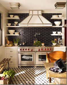 Floor. Backsplash. Bowls in the shelves. Veggies in the crate. Red knobs on the stove.