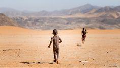 Un jeune garçon Himba court pour rattraper un membre de sa famille dans la région de Kunene, en Afrique, en Namibie.
