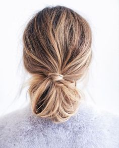 This low messy bun complete with a simple knot is perfect for the weekend or a workday hairstyle.
