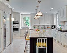 Kitchen: Glass Door Refrigerator In Full White Kitchen. glass door refrigerator. white kitchen cabinet. black kitchen island. granite countertop. tile flooring. industrial style pendant light. metal barstools.