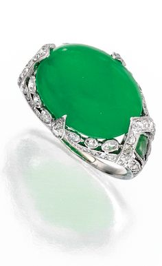 *PLATINUM, JADEITE AND DIAMOND RING Centering an oval-shaped jadeite cabochon measuring approximately 15.6 by 11.6 by 5.1 mm, flanked by two kite-shaped jade cabochons, the mounting further set with old European and single-cut diamonds weighing approximately .70 carat, size 5¾; circa 1920.