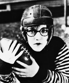 Mildred Davis dons a football uniform and husband Harold Lloyd's famous specs to pose as his college-boy character in The Freshman (1925)