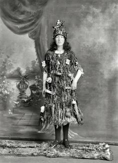 """New Zealand circa 1910. """"Studio portrait, young woman in Christmas tree fancy dress and hat costume, with little presents and decorations hanging off her, Christchurch."""" Half-plate glass negative by Adam Maclay."""