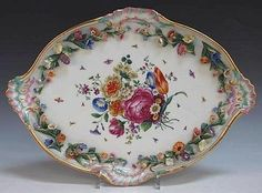 A late 19th Century Meissen porcelain oval tray, painted with a central spray of flowers framed by a flower encrusted border within a rococo scroll