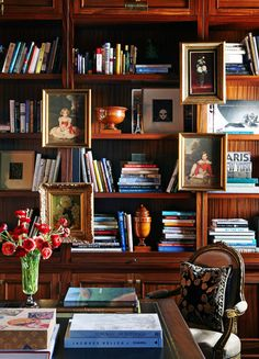 Hanging framed art over a bookcase helps to add dimension to a space - Traditional Home® / Design: Tim Clarke