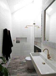 The master bath has a tumbled marble floor, brass fixtures, and a skylight for natural light. #remodelista #bathroom #masterbath #bathroomdesign #interiordesign