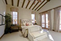Master bedroom with exposed wood beams, ceramic tile floor and teak wood doors.