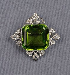Edwardian Platinum, Peridot, and Diamond Brooch/Pendant, Marcus & Co., bezel set with a square shaped peridot measuring approx. 14.70 x 14.50 x 7.20 mm, with rose-cut diamond accents, millegrain details, lg. 1 1/4 in., maker's mark.