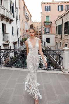 Sheath wedding dress with deep V-neckline, embroidery, and fringe skirt