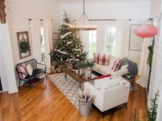 The living room of the newly renovated Magnolia House bed and breakfast has been completely transformed. Walls were removed to open the space, new windows and flooring were installed and shiplap now brightens up the space, as seen on Fixer Upper. (after)