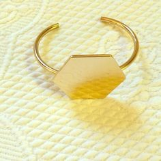 Gold Hexagon Bangle Bracelet Gold hexagon bangle bracelet. Perfect for a minimalist! Small imperfection on front, a dent in the metal, but not very visible. Never worn. ASOS Jewelry Bracelets