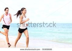 stock photo : sport - couple running on beach training for marathon run. Young multiracial couple runners, smiling asian female fitness model and caucasian male model.