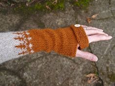 A quick and easy remedy against a chilly spring, these armwarmers can be readily knit from stash oddballs or leftovers from other projects. A dash of stranded colorwork and a faux button detail add eye-catching style.