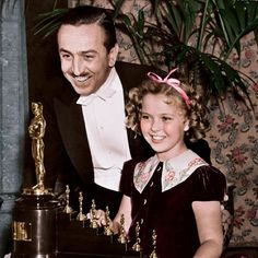 Walt Disney and presenter Shirley Temple with his Oscar (and seven mini Oscars) for Snow White and the Seven Dwarfs, 1939.