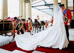 Prince Harry fixing the train on Kate Middleton's gown at her wedding to Prince William as they arrive at Buckingham Palace for the first of the two wedding receptions to celebrate their marriage.