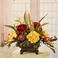 The vibrant  and bold colors is what you'll love about this silk floral design. Arranged with butter hydrangeas and magnolias, Burgundy ranunculus, orchids, heather grasses and feathers. Accented with a feather ball. Set in a brown Resin Rectangle Vase