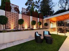 vier dekorative Cortenstahlplatten am Gartenmauer befestigt