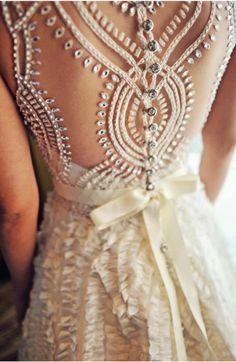 Beautiful open backed wedding dress with ruffles and a bow. Check out that elaborate detailing!
