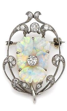 An opal and diamond pansy brooch, circa 1905 The opal finely carved to depict a pansy in bloom, centrally-set with an old brilliant-cut diamond, to a scrolling openwork surround millegrain-set with similarly-cut diamonds Opal Jewelry, Jewelry Art, Antique Jewelry, Vintage Jewelry, Fine Jewelry, Jewelry Design, Bijoux Art Nouveau, Art Nouveau Jewelry, Diamond Brooch
