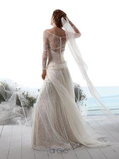 Abito di pizzo con maniche lunghe e sopragonna di organza. Lace dress with long sleeves and an organza overskirt.