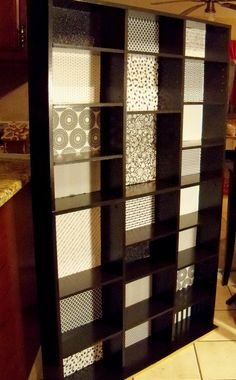 Bookcase made from decoupaging background papers and painted black, made from a DVD organizer.