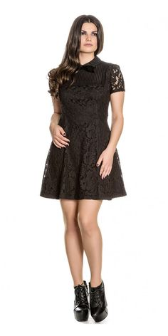 This lovely lacy Rowena Mini Dress is a wonderful new little black dress. This floral beauty is packed with sumptuous details. This simple skater style dress has short lace sleeves, a high neck with a small round lace collar and cute velvet bow detail. The chest has a square sheer panel with lace trim on the fitted bodice adding to the great textured design of this dress. The short A-line skirt flares from the waist and the top layer of floral lace are sewn into a black slip.