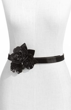 A pretty trio of sculpted leather roses adorns the buckle of a smooth faux-leather belt. $17.90