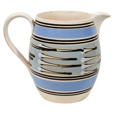 """A slip covered, machine turned Mocha jug with broad bands of light blue and thin lines of black at the top and bottom. The center with slip cup decoration in white, black and orange on a light blue gray ground. For an almost identical jug with coloring in tones of brown see Jonathan Rickard """"Mocha and related dipped wares, 1770-1939 figure 161 pg 113 which describes that jug: """" A pearlware barrel-form jug, slip banded with highly unusual three chambered slip cup decoration British c1830 7""""…"""