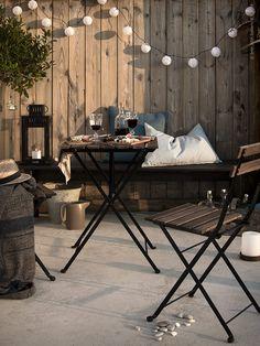 Njutbara sommarkvällar med TÄRNÖ bord + stolar, GURLI pläd, ÄNGSÖ bänk, BORRBY lykta, REMVALLEN kuddfodral,  SKRUV ljusslinga, SOLVINDEN dekoration för ljusslinga.