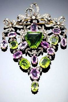 Beautiful EDWARDIAN PERIDOT, PINK TOPAZ AND DIAMOND BROOCH/PENDANT, CIRCA 1900. The central swing pendant designed as a garland composed of rose- and circular-cut diamonds with vari-cut peridots and pink topaz constructed in yellow gold and platinum.