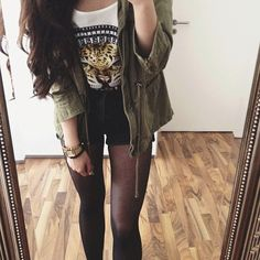 Black tights, shorts, moto boots, white graphic tee with green Army jacket.