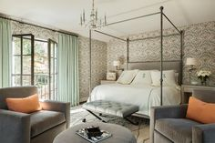 Beautiful bedroom features an iron canopy bed accented with a gray linen headboard dressed in white and green monogram bedding flanked by gray fabric nightstands with silver nailhead trim illuminated by swing arm sconces.