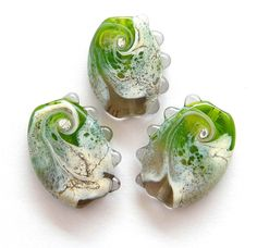 The beads have base in transparent gray and transparent green swirled together with silvered ivory shards and decorated with dots on one edge.    The beads have been etched to give a soft matte finish.