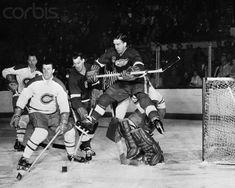 Nous sommes lors de la 4e game des séries de la Coupe Stanley le 8 avril 1950. Les Red Wings perdaient 3-0, les Canadiens en étaient à leur 4e victoire contre l'équipe adverse. De gauche à droite: Doug Harvey, Claude Provost, Gordie Howe des Red Wings, Ted Lindsay qui a les pattes dans les airs et Jacques Plante, le gardien.